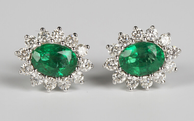 A pair of 18ct white gold, emerald and diamond earrings, each claw set with an oval cut emerald with