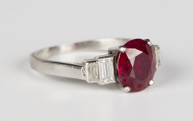 A ruby and diamond ring, claw set with an oval cut ruby between baguette cut diamond graduated two s