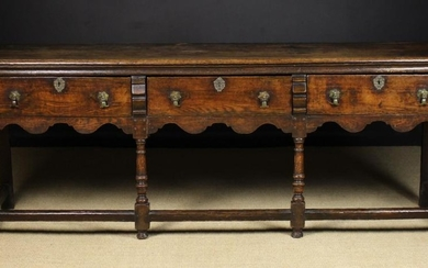 An 18th Century Dresser Base. The top having a moulded edge over three frieze drawers fitted with el