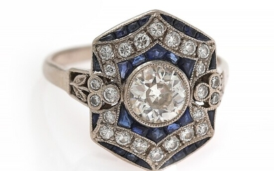 An Art Deco sapphire and diamond ring set with a diamond weighing app. 0.80 ct. encircled by numerous diamonds and sapphires, mounted in platinum. Size 54.