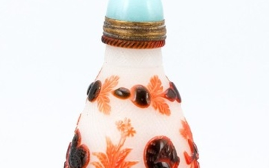"""CHINESE OVERLAY GLASS SNUFF BOTTLE In teardrop form, with red and orange bird and leaf decoration on a stippled ground. Height 2.25""""..."""