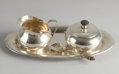 Handmade silver cream set, 800/000, with a milk jug, sugar bowl and a tray. Round model milk jug and sugar bowl with a lid with a wooden knob placed on an oval tray. All equipped with a hammer blow treatment. With silver sugar spoon with floral...