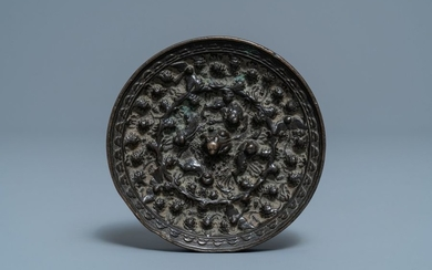 A Chinese bronze mirror with relief design, Tang...