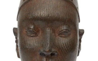 A bronze female head, Yoruba, in the...