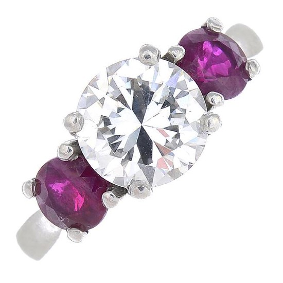 A diamond and ruby three-stone ring. The brilliant-cut