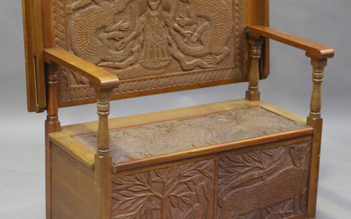 A late 20th century African carved hardwood monk's bench, the hinged box seat and front carved