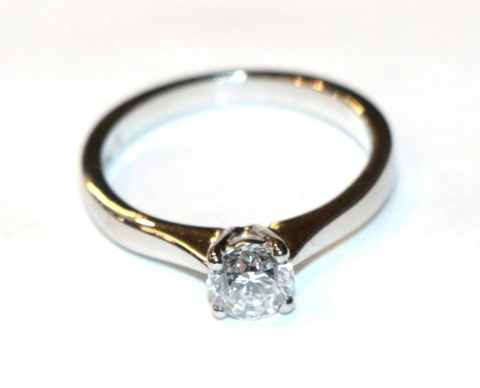 A platinum diamond solitaire ring, a round brilliant cut diamond...