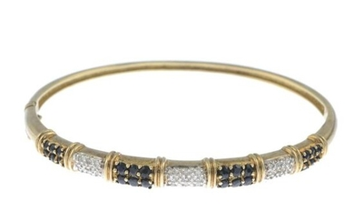 A sapphire and diamond bangle.Estimated total diamond weight...