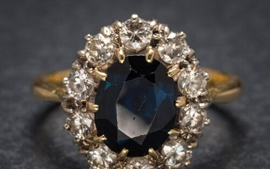 A sapphire and diamond oval cluster ring: the central oval s...