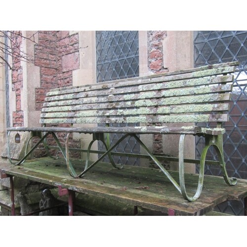 A sprung steel park/garden bench with weathered timber lathe...