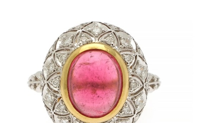 A tourmaline and diamond ring set with a cabochon pink tourmaline and numerous brilliant-cut diamonds, mounted in in 18k gold and white gold. Size 55.