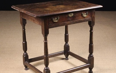 An 18th Century Oak Side Table. The top with moulded edge above a frieze drawer with brass swing han