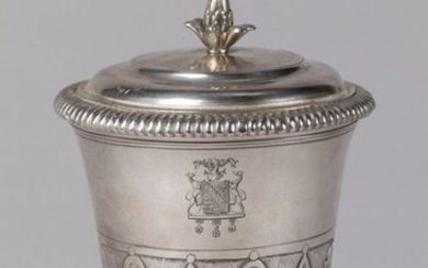 POT-À-FARD, or TIMBALE TULIPE COUVERTY of the Louis XIV period in silver, decorated at the half of the body with motifs of mantling alternating with lanceolate leaves. Pedestal with gadrooned frieze. The neck is underlined with fillets. The lid has a...