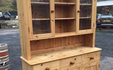 A pine dresser with moulded cornice above leaded glass...