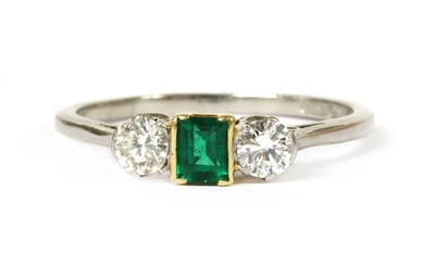 A platinum and gold, emerald and diamond three stone ring