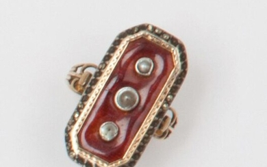 Hexagonal gold and silver ring enamelled red, decorated with three half pearls in a hematite surround. Finger size: 53. Gross weight: 3.6g. (missing)