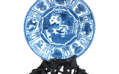 A very well-carved dense blackwood 'lotus pond' plate stand displaying a 'Kraak porcelain'-style saucer dish
