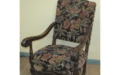 A 19c walnut framed and upholstered open arm chair with bold...