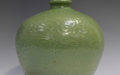 A Chinese celadon glazed vase, Ming style but probably Qing dynasty, of stout ovoid form, carved in
