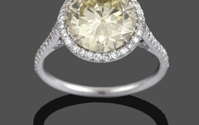 A Diamond Cluster Ring, a fancy intense yellow round brilliant...