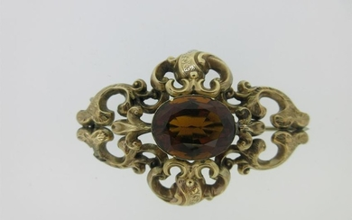 A Victorian citrine brooch in an ornate mount,