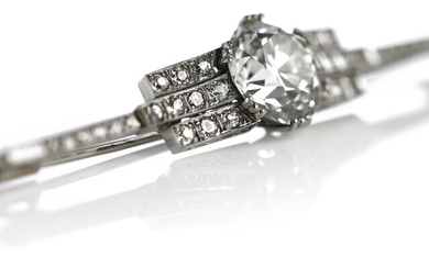 A diamond brooch set with an old-cut diamond weighing app. 5.95 ct. flanked by numerous single and old-cut diamonds, mounted in 14k white gold. K/VS1. 1930–40.