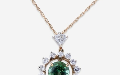 A green tourmaline and diamond pendant designed as a...