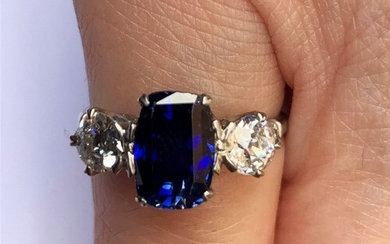 A sapphire and diamond three stone ring, the central cushion...