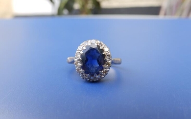 An oval sapphire & diamond cluster ring on '18ct'...