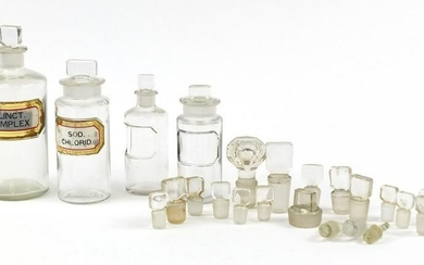 Four antique glass apothecary jars and extra stoppers