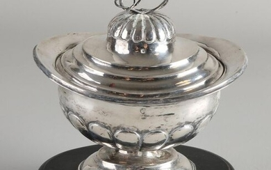 Silver tobacco jar, 833/000, oval model with fluting on oval base with a lid with fluting and swirl, flower is missing. The whole is placed on an oval black wooden base. MT .: Alexander Mentz Leeuwarden, 1843-1856. 16x13x18cm. Edge slightly out of...
