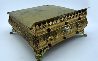THABOR forming MISSEL HOLDER in bronze and gilt metal. It rests on four lion paw legs, it is openworked with foliage and set with cabohons of coloured glass. The top is decorated with a cross in a quatrefoil. 15.5 x 28 x 31 cm.