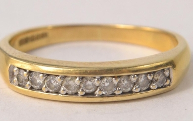 750 stamped gold ring with a multi faceted diamond upper ba...