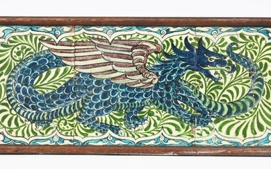 A William De Morgan Dragon three tile panel, the dragon modelled standing its tail wrapped back around its body, on foliate panel ground, in shades of blue, green, turquoise and aubergine on a white ground, framed, damages, 20.5cm. square