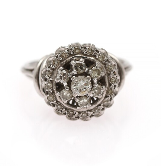 A diamond ring set with a brilliant-cut diamond encircled by numerous single-cut diamonds, mounted in 18k white gold. Size 52. Circa 1950s.