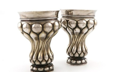 A pair of continental silver beakers, bearing pseudo 18th century Russian marks, tapering lobed form, plain rim, on raised lobed bases, height 18cm, approx. weight 29oz. (2) Provenance: The late Greta Morrison, widow of Bryan Morrison.
