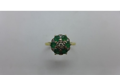 An 18ct gold emerald and diamond cluster ring with an illusi...