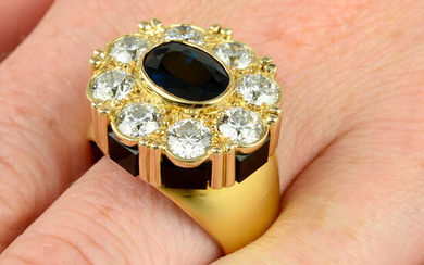 An 18ct gold sapphire and brilliant-cut diamond cluster ring, with onyx panel gallery.