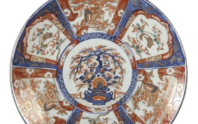 Big plate with Imari decor Japan, 20th century, porcelain, underglazed blue and onglazed red decor in cartouches framed with representations like vases, ornamental trees and rodents, decorated with ornamental gold, d: 46 cm. Burn mark, chip.