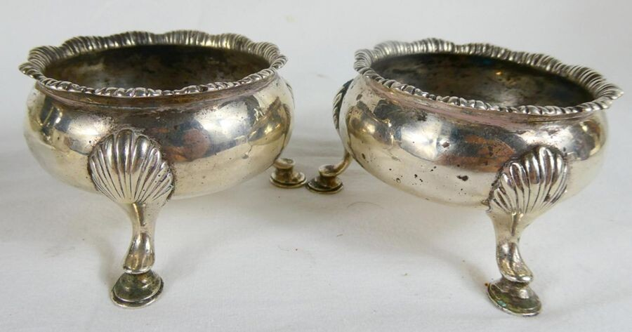 Classic pair of Georgian Sterling Silver Salt Cellars with gadrooned rims and hoof feet. Weight 152 grammes. Hallmarked London 1774 - makers mark David Hennell. Diam 7cm.