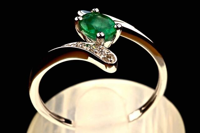 Designer ring in 18 karat white gold with certified oval Emerald of 0.447 carat and ring body with 1 line paved with natural brilliant-cut GH-SI diamonds for a total of 0.02 carat. size (can be modified) 54, 1.87g. Luxurious case.