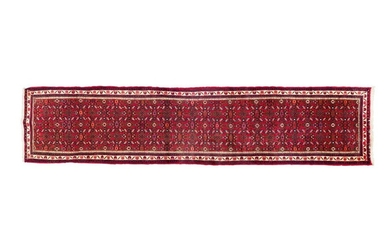 Gallery MELAYER (Iran) around 1985. Dimensions: 380 x 078 cm. Technical characteristics: Wool velvet on cotton foundations. Good general condition. Ruby field with Herati motifs, seedlings of flowers in the form of stylized diamond-shaped exploded...