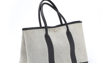"Hermès: A ""Garden Party Tote Bag"" of beige canvas and black leather with a large compartment with button closure, and two leather handles."