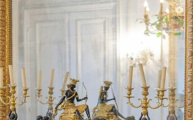 Pair of ormolu and patinated bronze candelabra representing an African woman carrying a bouquet of three lights. Resting on a shaft decorated with a palmette and on a square base.