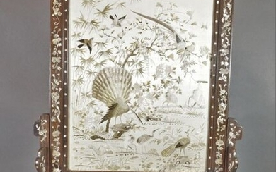 Screen composed of an embroidered silk panel decorated with peacocks, cranes and birds, the wooden frame inlaid with mother-of-pearl with lotus, bamboo and bat decoration. The wooden frame inlaid with mother-of-pearl decorated with characters and...