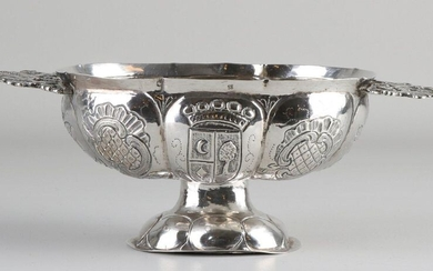 Silver brandy bowl, 833/000, oval lobed model decorated with driven family coat of arms, placed on an oval base and provided with handles of 2 standing lions wearing a crown. MT .: R. Huishuizen, Groningen, last year: K: 1819.24x12x9cm ca 193 grams...