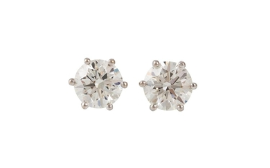 A PAIR OF DIAMOND SOLITAIRE STUD EARRINGS, with two round br...