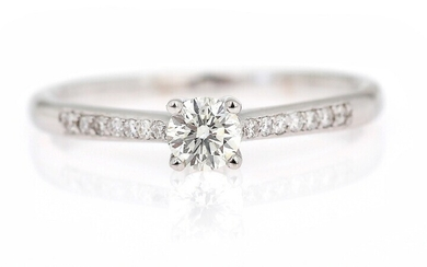 A diamond ring set with a brilliant-cut diamond flanked by numerous diamonds weighing a total...