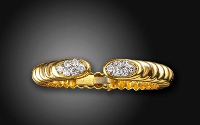 A diamond set gold bangle believed to be by Wander, the terminals set with clusters of gradauted round brilliant-cut diamonds to the ribbed gold bangle, diamonds 1.40cts total approximately, unsigned 5.2cm internal diameter, 44g total
