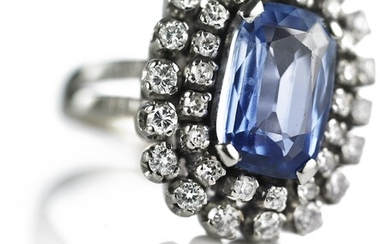 A sapphire and diamond ring set with a natural Ceylon sapphire weighing app. 3.50 ct. encircled by numerous diamonds weighing a total of app. 2.00 ct. Size 53.